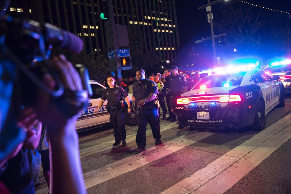 Bystanders stand near pollice baracades following the sniper shooting in Dallas on July 7, 2016. (Laura Buckman/AFP/Getty Images)