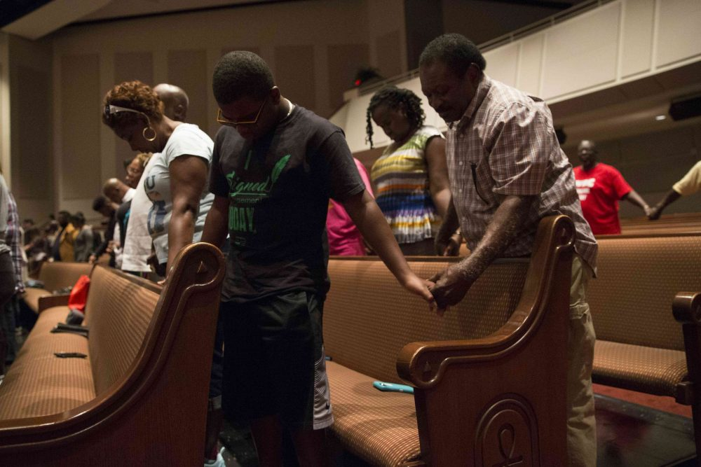 """Parishioners of Frienship-West Baptist Church in Dallas, Texas, pray together on July 10, 2016, during a """"Community Conversation"""" event following the recent sniper attacks against white police officers. The Dallas gunman was plotting a major bomb attack, authorities said, urging calm after more than 200 people were arrested in a new night of protests over police violence against blacks. (Laura Buckman/AFP/Getty Images)"""