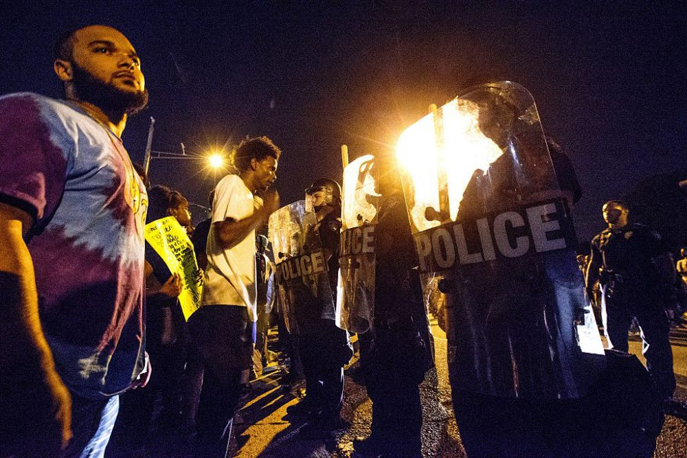 Protesters face off with Baton Rouge police in riot gear across the street from the police department on July 8, 2016 in Baton Rouge, Louisiana. Alton Sterling was shot by a police officer in front of the Triple S Food Mart in Baton Rouge on July 5th, leading the Department of Justice to open a civil rights investigation. (Mark Wallheiser/Getty Images)