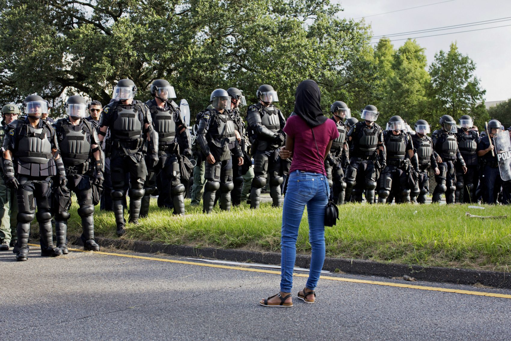 A protester watches as police in riot gear clear the street of protesters in front of the Baton Rouge Police Department headquarters in Baton Rouge, La., Saturday, July 9, 2016. (Max Becherer/AP)
