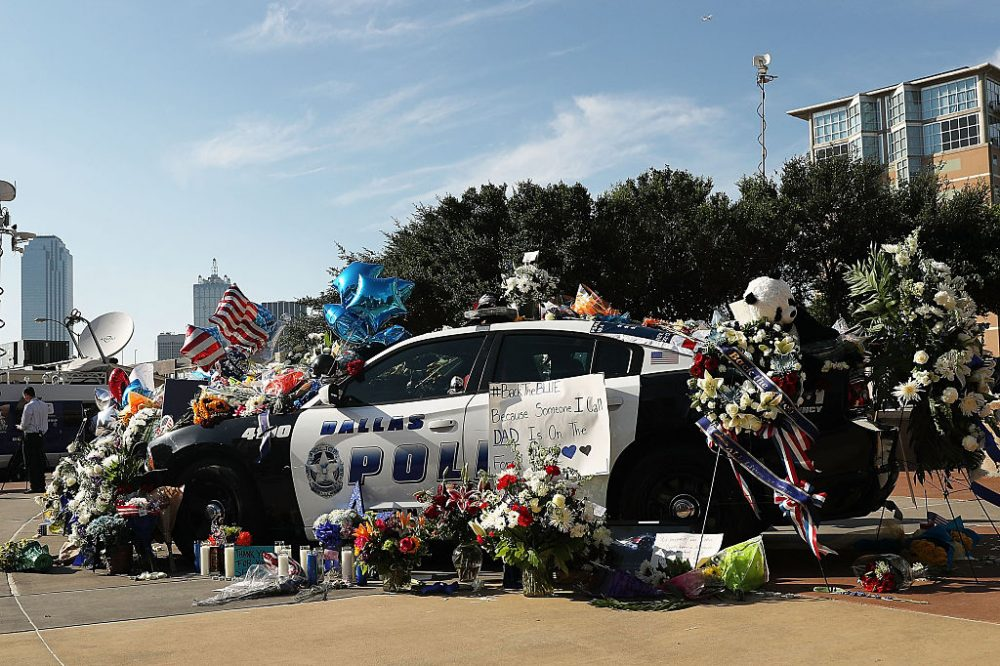 People write condolence notes and lay flowers at a growing memorial in front of the Dallas Police Headquarters near the area that is still an active crime scene in downtown Dallas following the deaths of five police officers on July 8, 2016 in Dallas, Texas. (Spencer Platt/Getty Images)