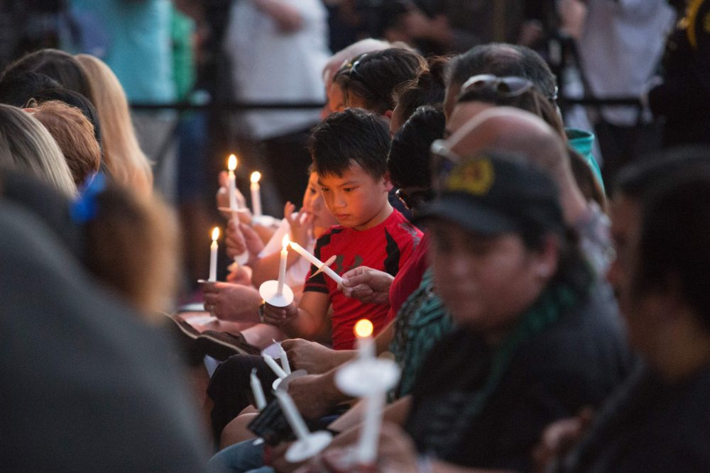 """A young boy sitting in the section reserved for family of the police officers killed in Dallas lights a candle during a """"Dallas Strong"""" event on July 11, 2016 in Dallas, Texas. (Laura Buckman/AFP/Getty Images)"""