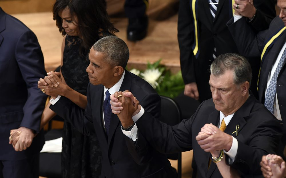 President Barack Obama holds hands with Dallas Mayor Mike Rawlings, right, and first lady Michelle Obama during an interfaith memorial service for the fallen police officers and members of the Dallas community in Dallas Tuesday. (Susan Walsh/AP)