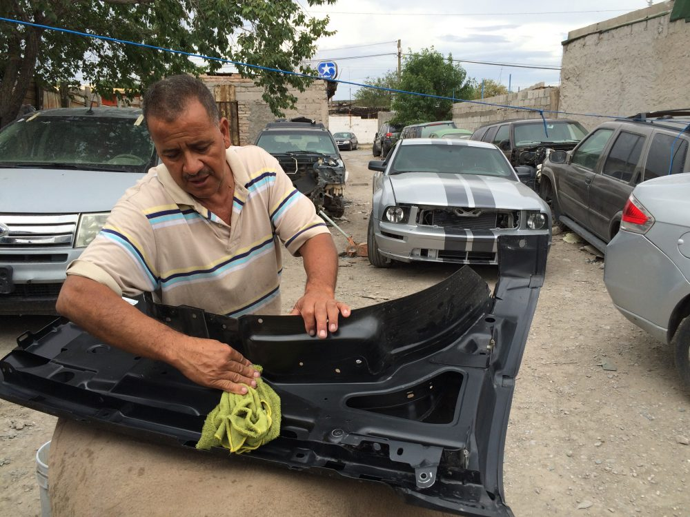 A worker at a body shop in Juárez cleans a fender that he'll install on a used truck imported from the U.S. (Mónica Ortiz Uribe/Fronteras)
