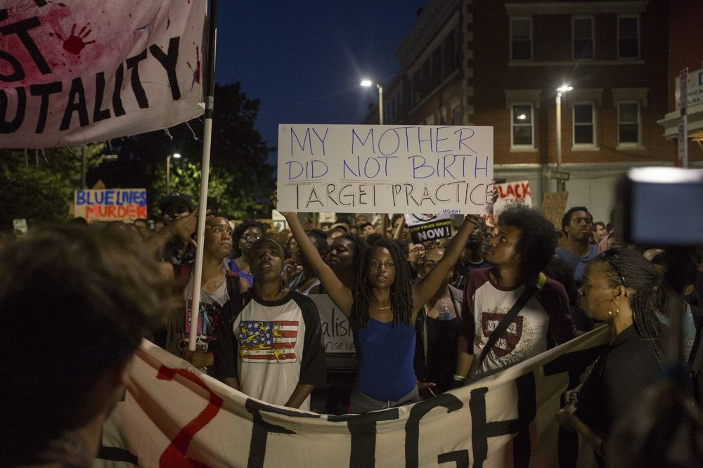 A woman holds up a sign in protest of police brutality at a rally in Boston that drew a significant crowd Wednesday night. (Joe Difazio/WBUR)