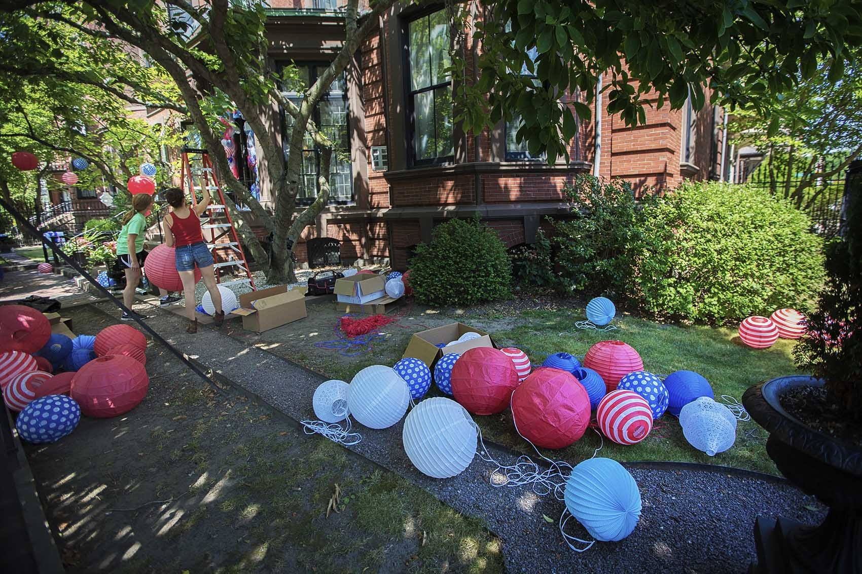 Volunteers set up red, white and blue lanterns for the French Cultural Center's annual Bastille Day celebration on Friday. (Jesse Costa/WBUR)