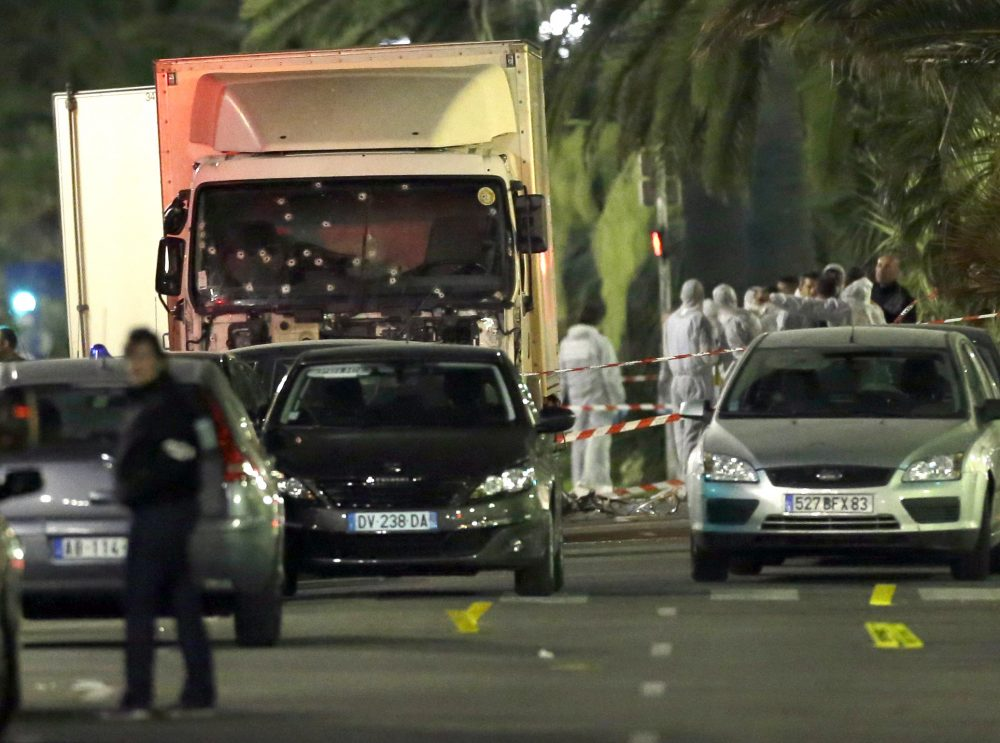 Forensic officers stand near a truck with its windscreen riddled with bullets, that plowed through a crowd of revelers who'd gathered to watch the fireworks in the French resort city of Nice, southern France, Friday, July 15, 2016. At least 80 people were killed before police killed the driver, authorities said. (Claude Paris/AP)