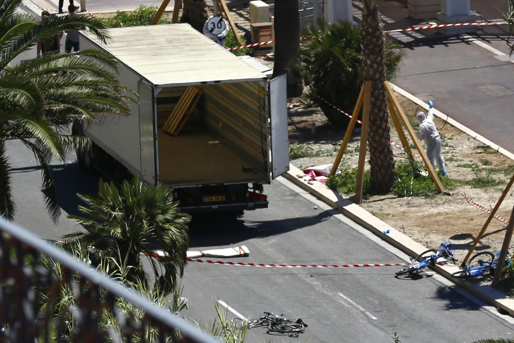 Police officers work near the truck that mowed through revelers in Nice, southern France, Friday, July 15, 2016.  A large truck mowed through revelers gathered for Bastille Day fireworks in Nice, killing more than 80 people and sending people fleeing into the sea as it bore down for more than a mile along the Riviera city's famed waterfront promenade.  (AP Photo/Francois Mori)