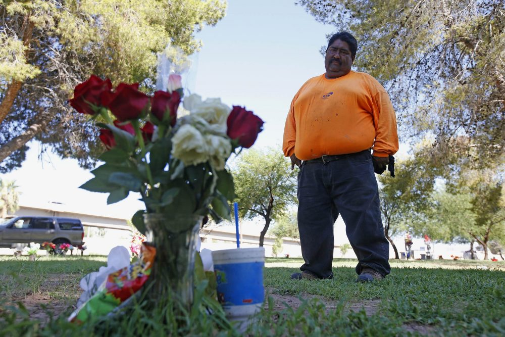 """Margarito Castro, father of Manuel """"Manny"""" Castro Garcia, 19, visits his son's grave at a cemetery Thursday, July 14, 2016, in Phoenix. The teen was killed in June, and is one of a growing number of victims associated with a serial killer according to police. (Ross D. Franklin/AP)"""
