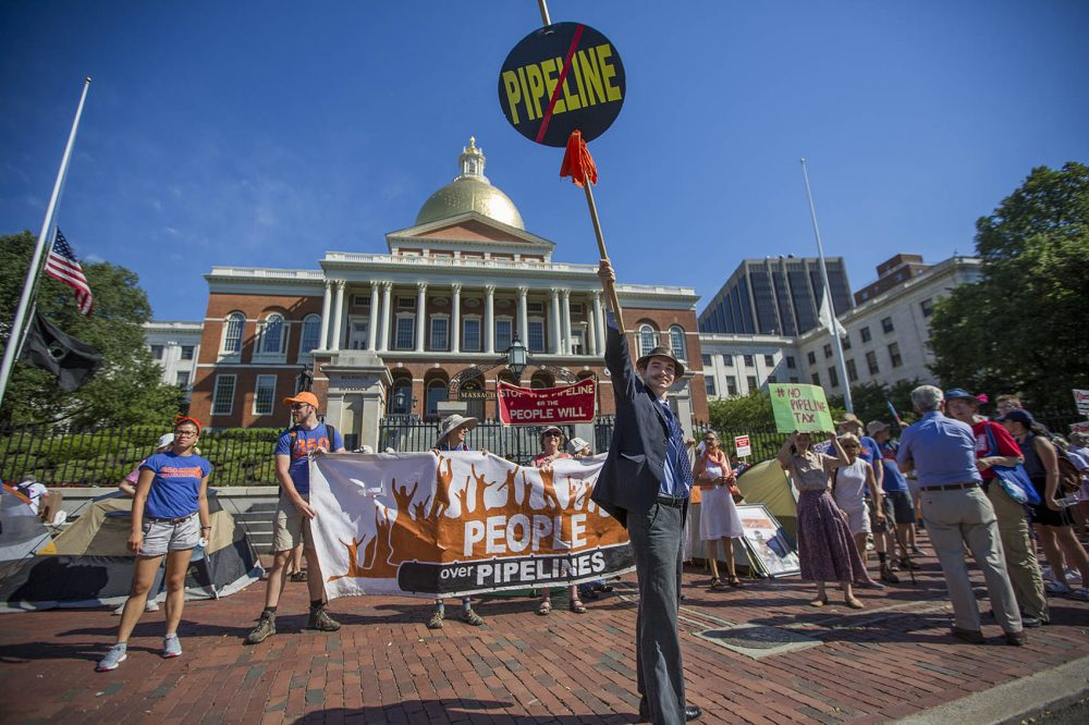 Tim Clancy, of West Roxbury, holds up a no pipeline sign in front  of the State House Monday. (Jesse Costa/WBUR)