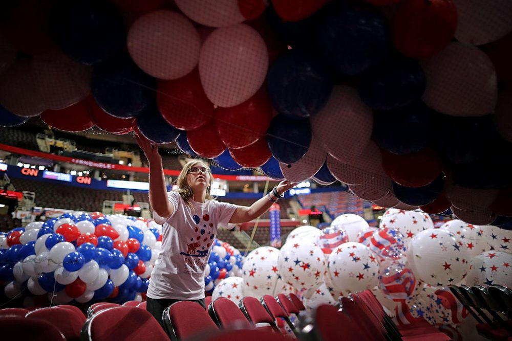 Volunteer June Fertiz, 15, with the band and choir group from Garfield Heights High School, helps move nets filled with thousands of red, white and blue balloons before they are lifted into the ceiling of the Quicken Loans Arena July 15, 2016 in Cleveland, Ohio.  (Chip Somodevilla/Getty Images)