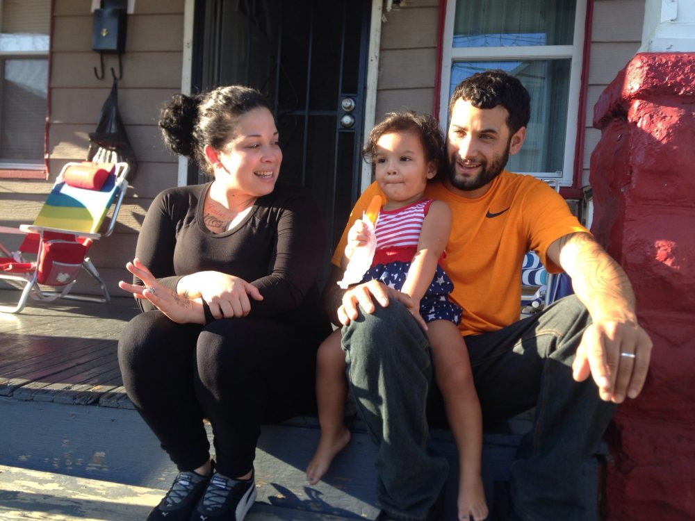 Cinthia Cruz (left) and her boyfriend Juan Rivera sit on their front steps with their daughter Zahira. Cruz and Rivera live in Cleveland, and make $1,400 a month to support their family.  (Peter O'Dowd/Here & Now)