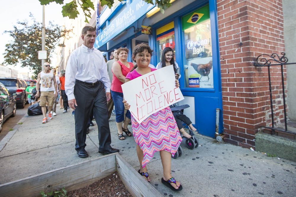 Eight-year-old Natalie Lemus walks with Mayor Marty Walsh down Chelsea Street during a neighborhood walk for peace in East Boston Tuesday night. (Jesse Costa/WBUR)