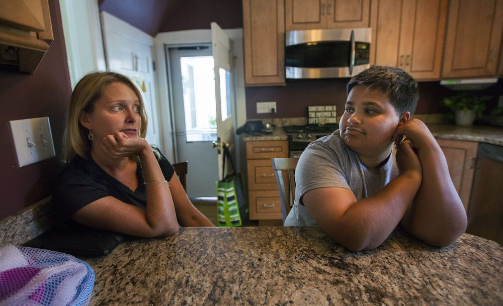Judy Tasker and her adopted transgender son Nathan chat in their kitchen. (Jesse Costa/WBUR)
