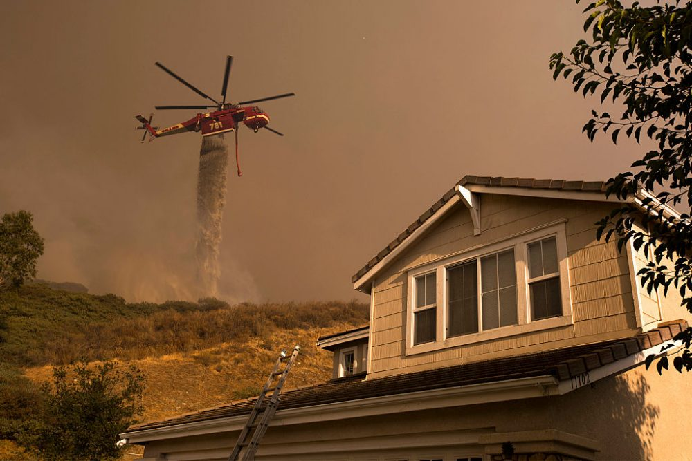 A firefighting helicopter makes a water drop near homes at the Sand Fire on July 24, 2016 in Santa Clarita, California. Triple-digit temperatures and dry conditions are fueling the wildfire, which has burned across at least 32,000 acres so far and is only 10% contained.  (David McNew/Getty Images)