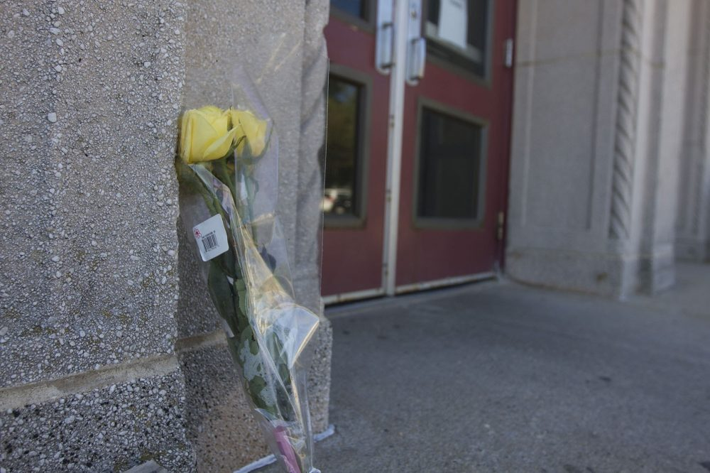 A lone flower is seen outside the Curley Community Center at Carson Beach in South Boston on Wednesday. The center's bathhouse is closed following the death of 7-year old Kyzr Willis. (Joe Difazio for WBUR)
