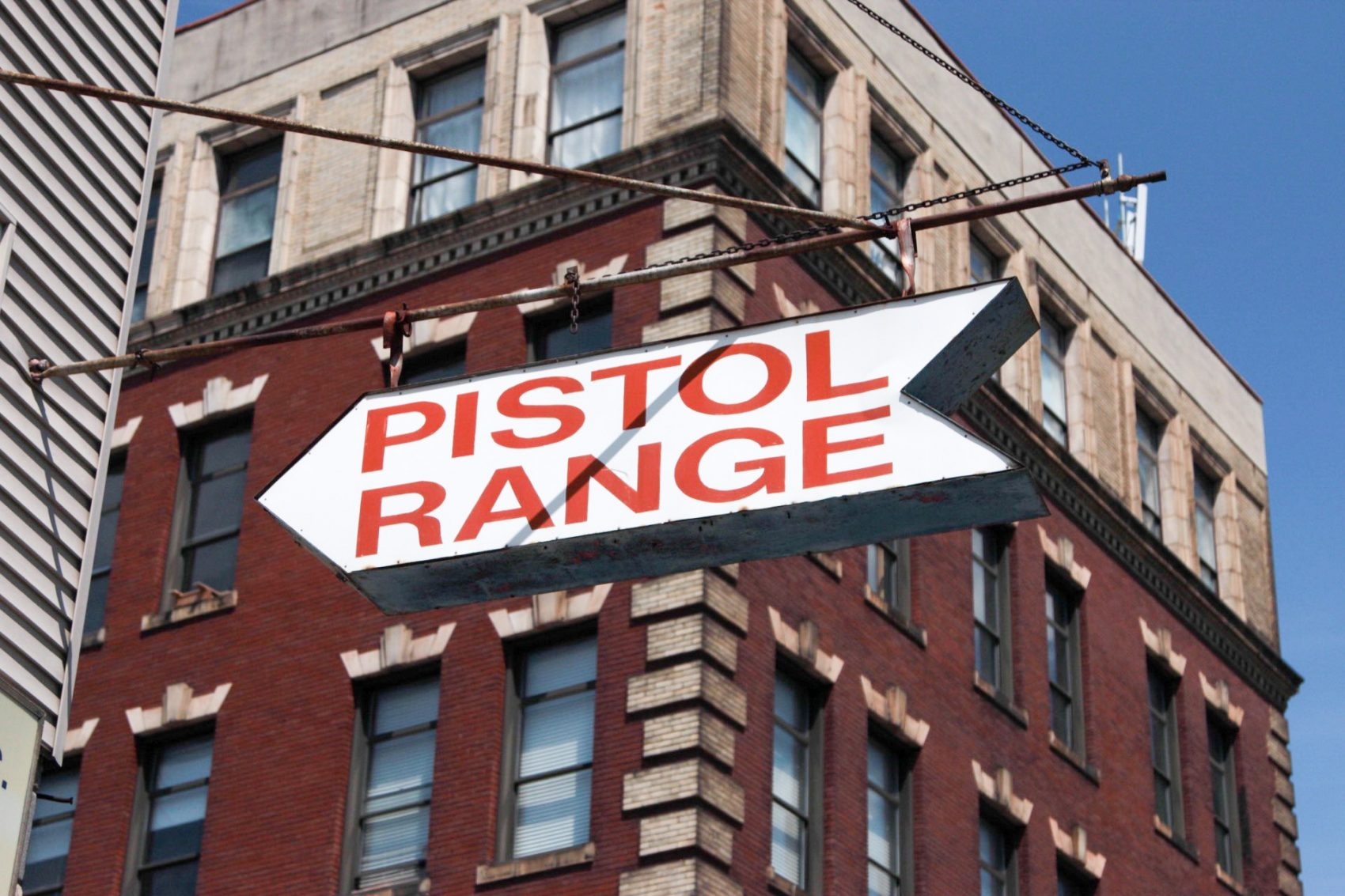 A sign on the corner of Spring Garden Street and North Percy Street points pedestrians to The Gun Range in North Philadelphia. (Dean Russell/Here & Now)