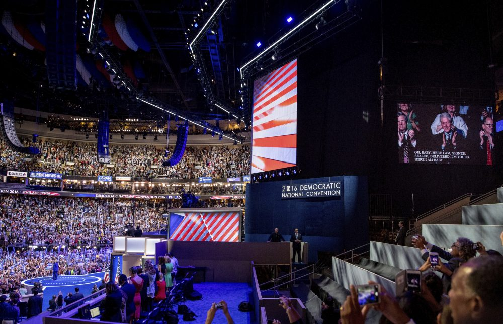 Former President Bill Clinton is shown on television, right, as President Barack Obama and Democratic presidential candidate Hillary Clinton appear on stage together at the DNC. (Andrew Harnik/AP)