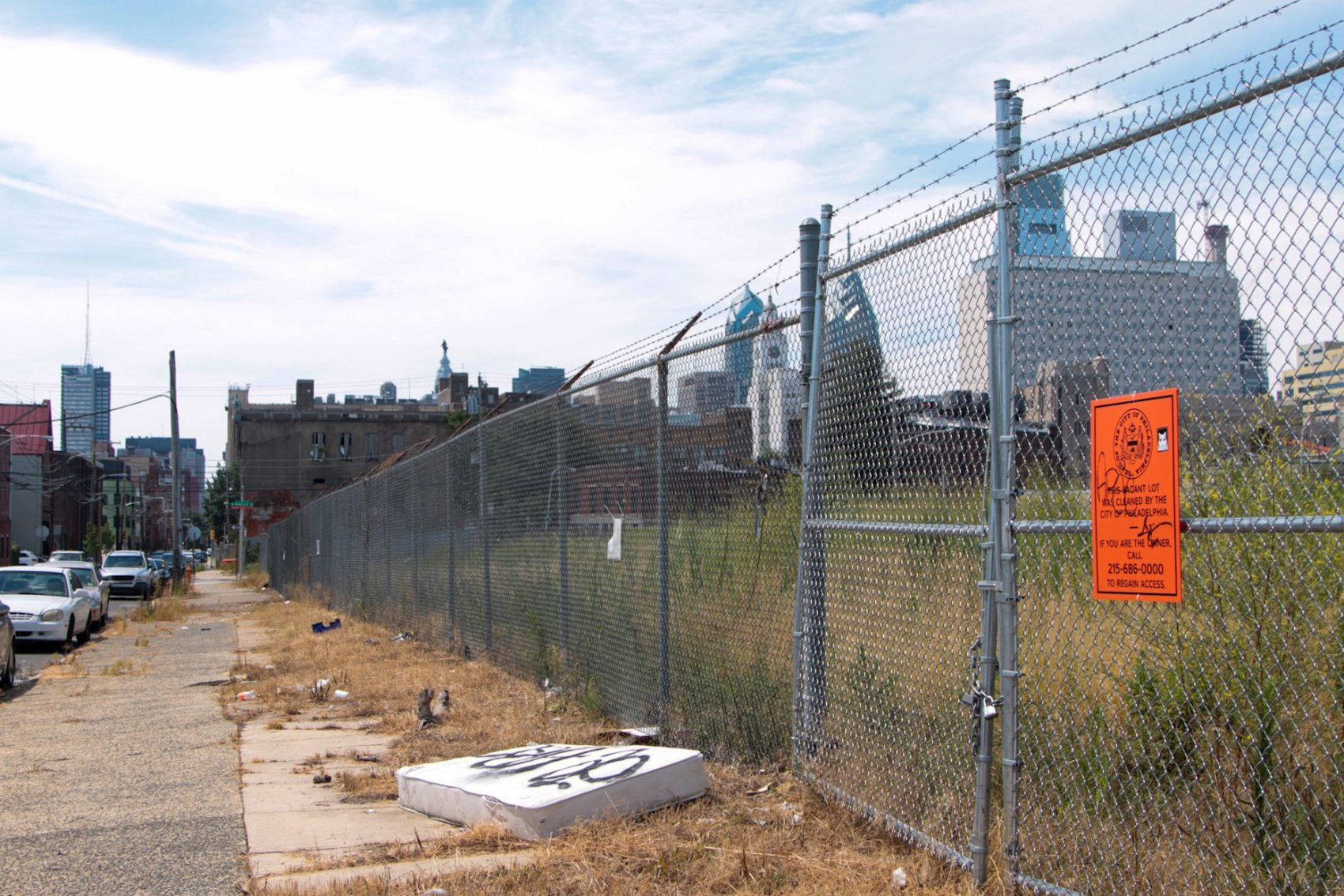 A fenced vacant lot on 13th Street in North Philadelphia. (Dean Russell/Here & Now)