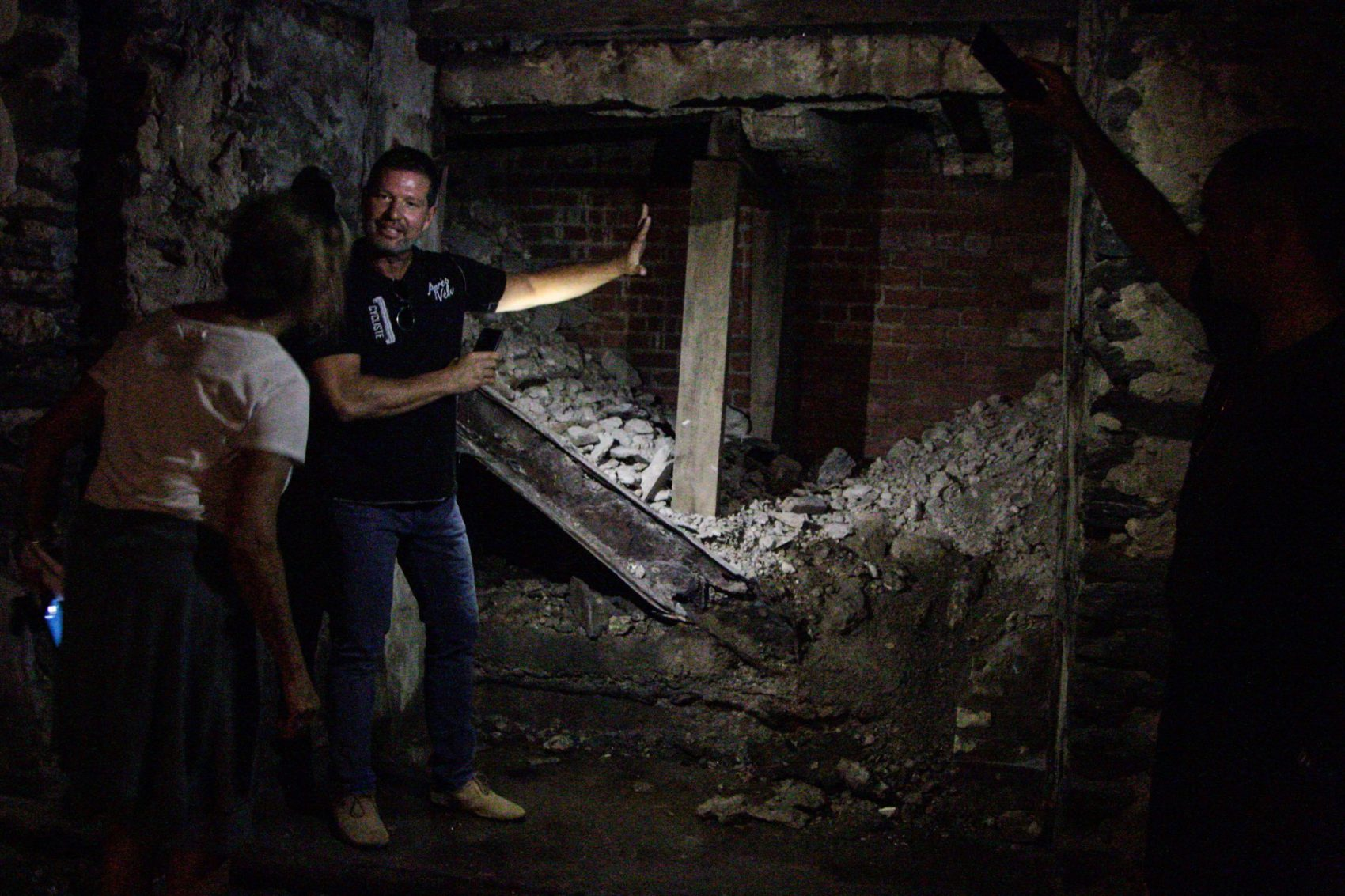 Eric Blumenthal, developer and owner of the Divine Lorraine Hotel building, shows Here & Now's Robin Young the basement level, which includes an old entrance to a Prohibition-era speakeasy. (Dean Russell/Here & Now)