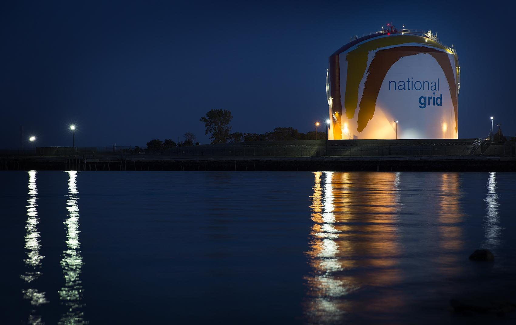 Corita Kent's rainbow gas tank reflects in the Dorchester Bay at night. (Robin Lubbock/WBUR)
