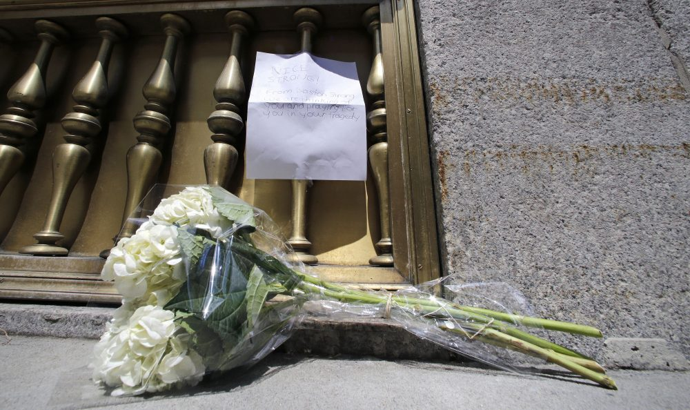 "A bouquet of flowers and a note wishing ""Nice Strong"" were left outside the entrance to the French Consulate in Boston. (Charles Krupa/AP)"