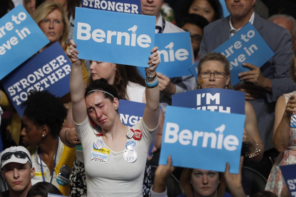 A disappointed Bernie Sanders supporter holds up her sign as Sanders speaks at the DNC Monday night. (Mary Altaffer/AP)