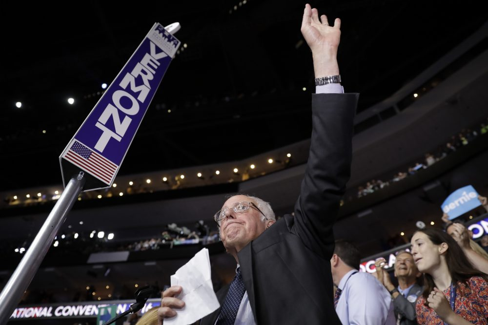 Sen. Bernie Sanders waves Tuesday evening from the floor of the DNC before asking delegates to accept Hillary Clinton's nomination unanimously and by acclimation.  (Matt Rourke/AP)