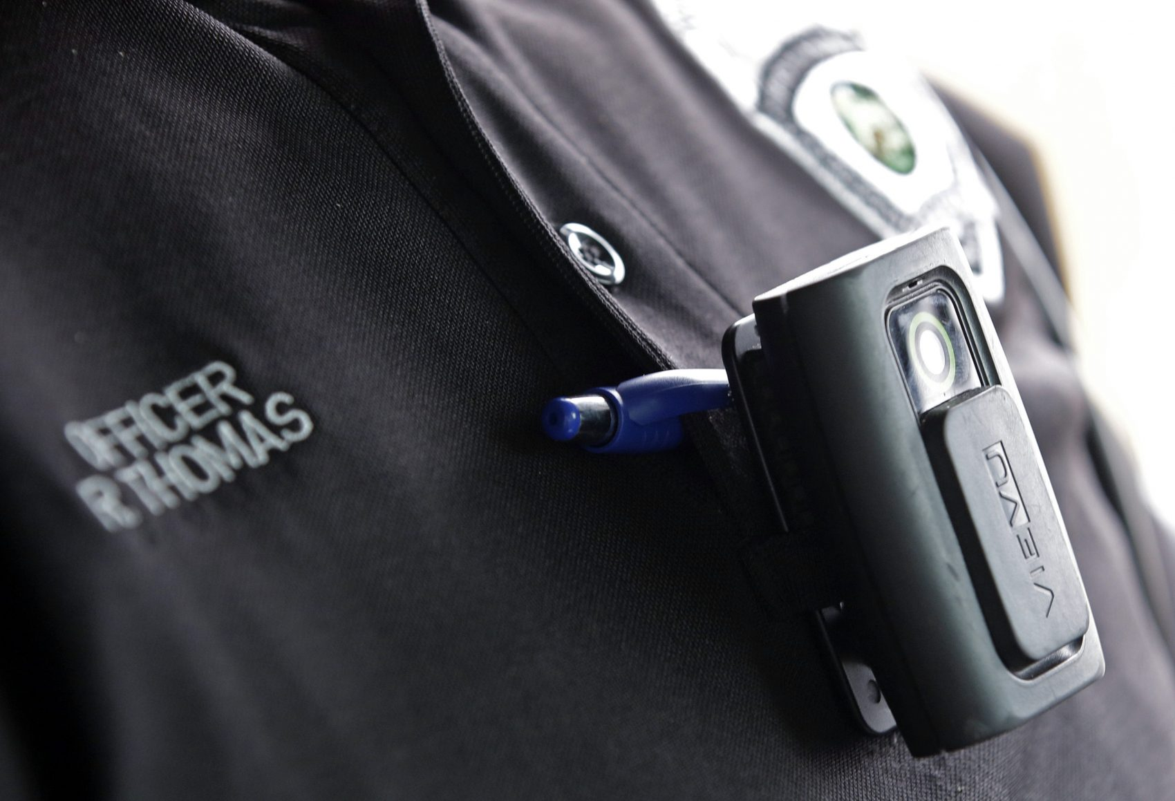 After recent police shootings, activists in Boston say they want police to move more quickly in implementing a body camera pilot program. Pictured: A body camera on an officer in Whitestown, Indiana. (Darron Cummings/AP)