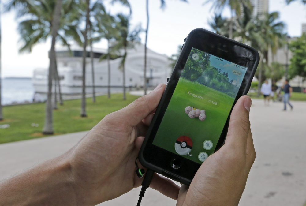 """Exeggcute, a Pokemon, is found by a  Pokemon Go player, Tuesday, July 12, 2016, at Bayfront Park in downtown Miami. The """"Pokemon Go"""" craze has sent legions of players hiking around cities and battling with """"pocket monsters"""" on their smartphones. It marks a turning point for augmented reality, or technology that superimposes a digital facade on the real world. (Alan Diaz/AP)"""