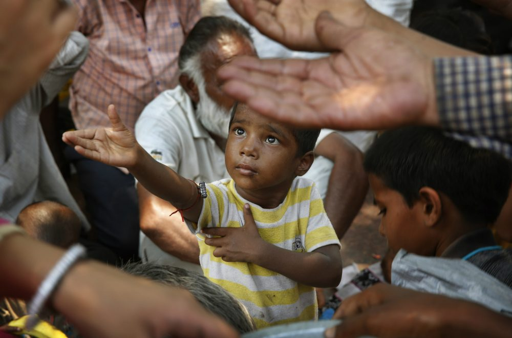 "Joelle Renstrom: ""People who struggle to meet basic needs such as food, water, shelter and security have bigger concerns than internet access."" Pictured: An Indian child stretches arms to receive free food being distributed outside a Hindu temple, in New Delhi, India, where countless children live with grinding poverty, sleep on sidewalks, beg at traffic intersections and rely on government-run lunch programs that often provide their only full meal for the day. (Manish Swarup/AP)"