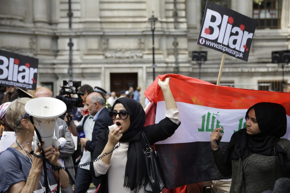 A British Iraqi protester holds up an Iraqi flag, during a protest, outside the Queen Elizabeth II Conference Centre in London, after the publication of the Chilcot report into the Iraq War. (Matt Dunham/AP)