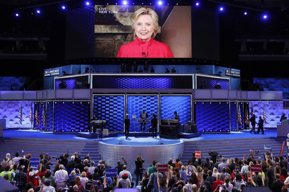 """Via live video from New York on the night of her nomination, Democratic presidential candidate Hillary Clinton tells the DNC crowd, """"We just put the biggest crack in that glass ceiling yet."""" (J. Scott Applewhite/AP)"""