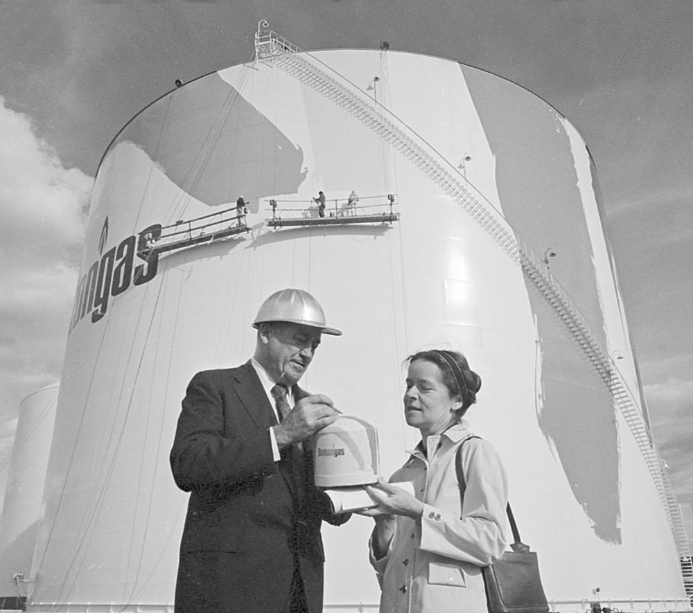 As painters cover 150-foot-high tank with rainbow stripes, artist Corita Kent and Karl Kunberger, manager of gas supply and construction, look at a finished model, on Oct. 19, 1971. (AP)