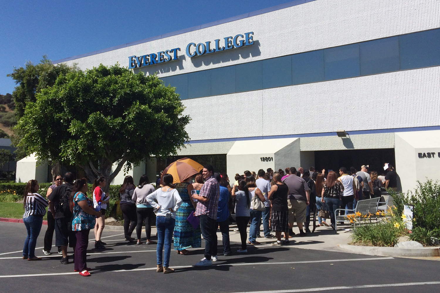In this April 28, 2015 file photo, students wait outside Everest College in Industry, Calif., hoping to get their transcripts and information on loan forgiveness and transferring credits to other schools. (Christine Armario/AP)