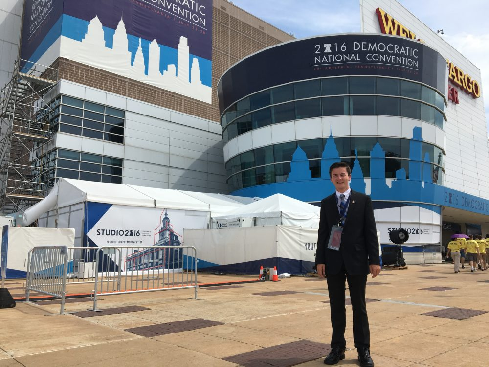 Trevor Doiron, 17 -- one of the youngest delegates at the Democratic National Convention --  stands in front of the Wells Fargo Center entrance, where the convention is being held in Philadelphia. (Shannon Dooling/WBUR)