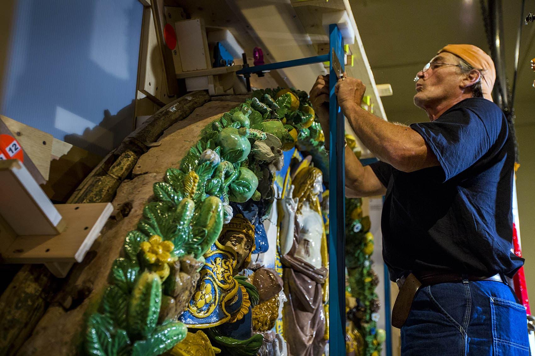 "Installers delicately mount the Gionvanni della Robia relief of the ""Resurrection of Christ"" at the Museum of Fine Arts in Boston. (Jesse Costa/WBUR)"