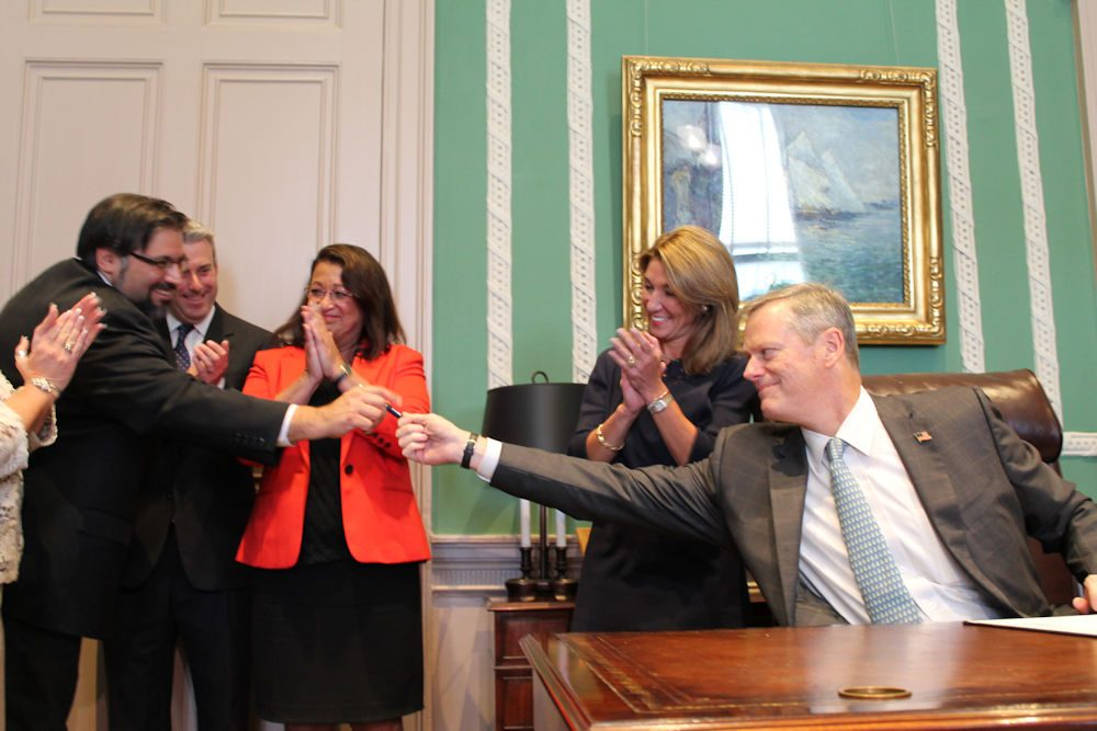 After signing legislation to regulate the state's ride-hailing industry, Gov. Charlie Baker thanked Deputy Chief of Staff Joel Barrera for his role in advancing the measure, and handed him the first pen he used to sign the bill into law. (Antonio Caban/State House News Service)