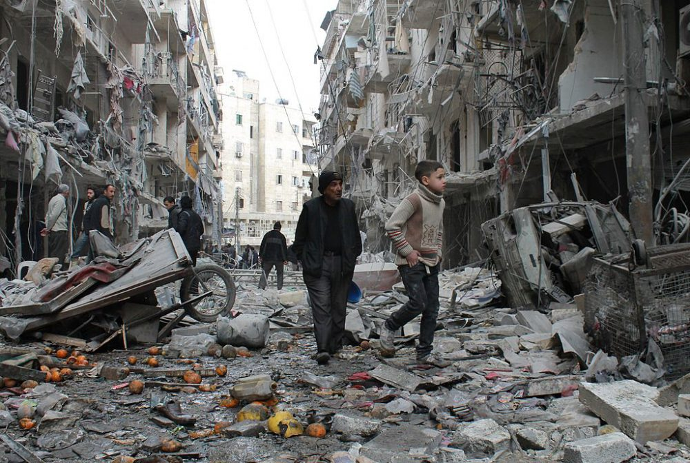 An elderly Syrian man and a child walk amidst debris in a residential block reportedly hit by an explosives-filled barrel dropped by a government forces helicopter on March 18, 2014 in Aleppo. (Baraa Al-Halabi/AFP/Getty Images)