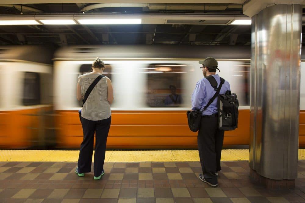 Commuters wait on the platform as an Orange Line train enters Downtown Crossing station. (Jesse Costa/WBUR)