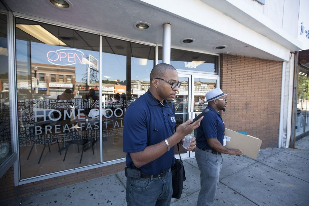 Manny Allen, manager of the Boston Public Schools reengagement center, left, and Rajon Brooks, an outreach manager with the center, begin their day of engaging with chronically absent students at Brothers Deli in Mattapan. (Joe Difazio/WBUR)