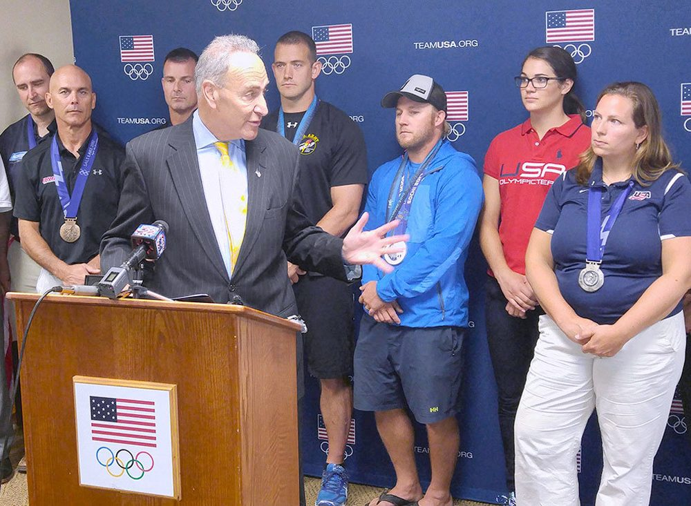 Sen. Chuck Schumer (D-NY) at the podium speaking about his campaign against Olympic medal taxes in Lake Placid, New York. (Brian Mann/NCPR)