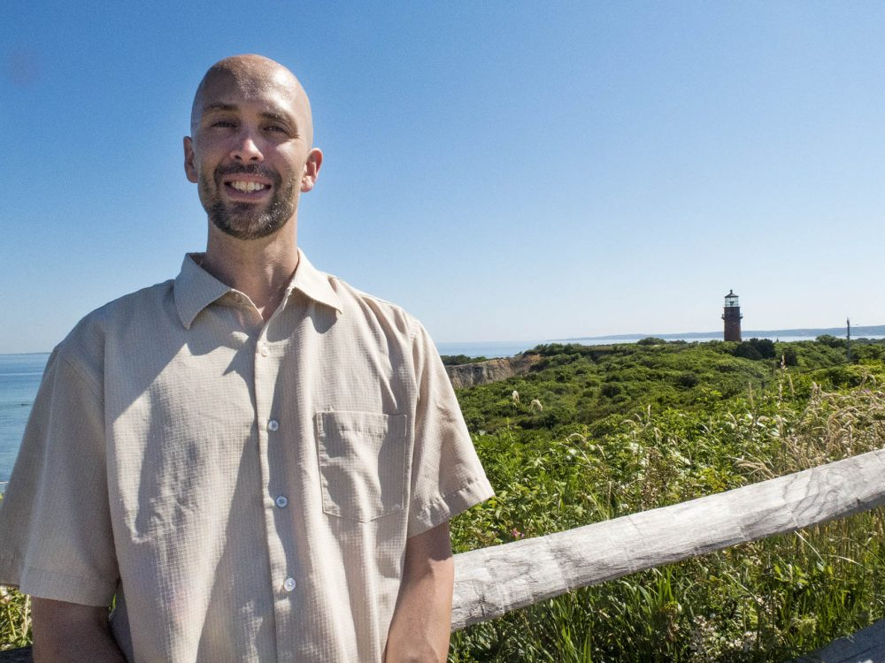 Durwood Vanderhoop, planner for the Aquinnah tribe, in front of historic Gay Head Light (Andrea Shea/WBUR)