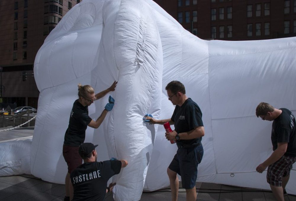 """Doug Lane (center) and his Fastlane Productions team clean one of five inflatable rabbit sculptures by Australian artist Amanda Parer that appeared in Denver in June as part of a series called """"Intrude"""" commissioned by Arts Brookfield. (Corey H. Jones/CPR News)"""