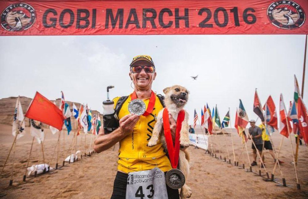 Scottish ultramarathoner Dion Leonard stands at the finish line of the Gobi March in China, holding Gobi, a stray dog who ran alongside him for most of the 155-mile race. (Courtesy of Bring Gobi Home via Facebook)
