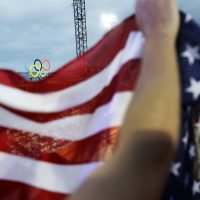 The Olympic rings are seen atop the beach volleyball venue as spectators wave an American flag at the 2016 Summer Olympics in Rio de Janeiro, Brazil, Monday, Aug. 8, 2016. (David Goldman/AP)