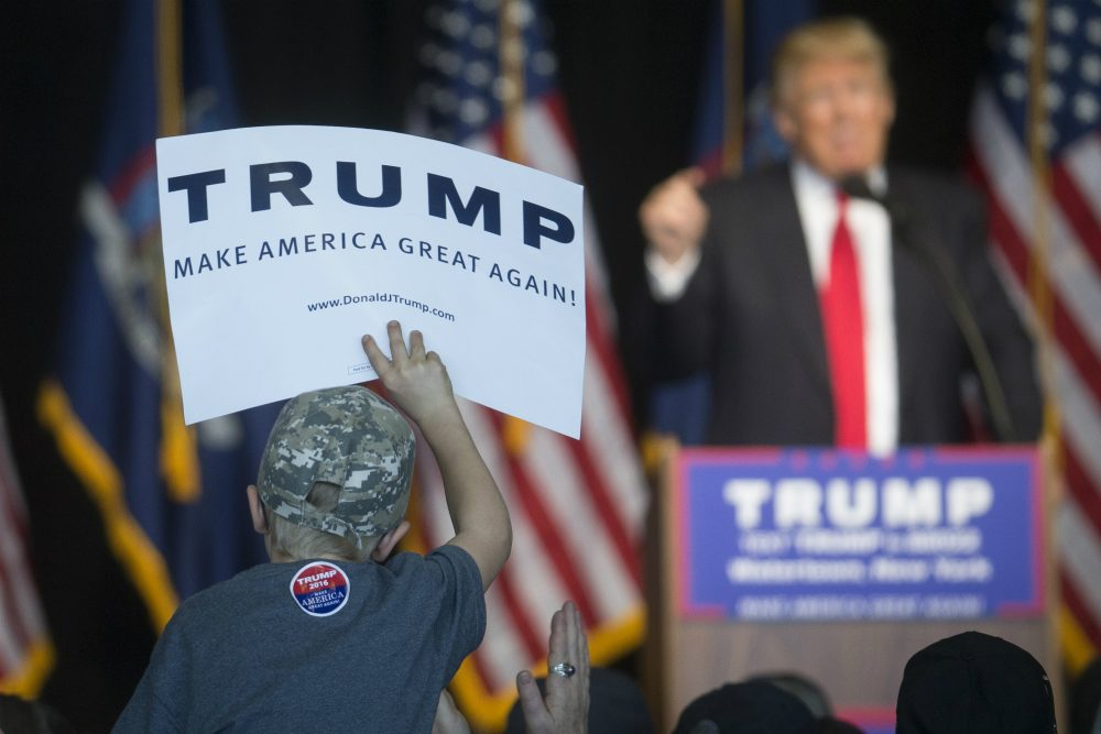 A young attendee holds a sign supporting Republican presidential candidate Donald Trump, right, as he speaks during a campaign event at Watertown International Airport, Saturday, April 16, 2016, in Watertown, N.Y. (John Minchillo/AP)