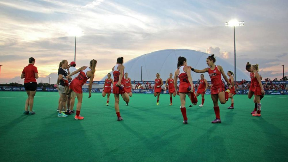 Olympic field hockey players stretch on the turf field at Spooky Nook in Manheim, Pennsylvania. (Emma Lee/WHYY)