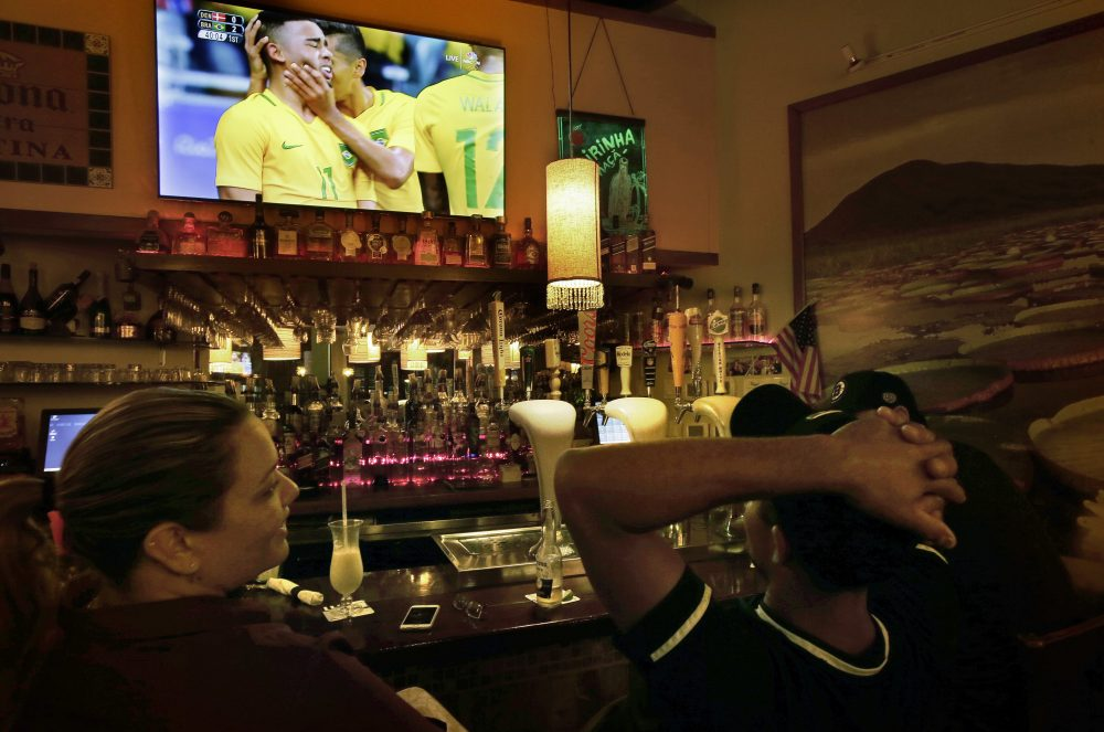 Camila Ornelas, left, and Vander Junior, right, both originally of Brazil, watch a televised soccer match between Brazil and Denmark at the Rio Olympics on Wednesday while sitting at the bar in the Tropical Cafe, in Framingham, Mass. (Steven Senne/AP)