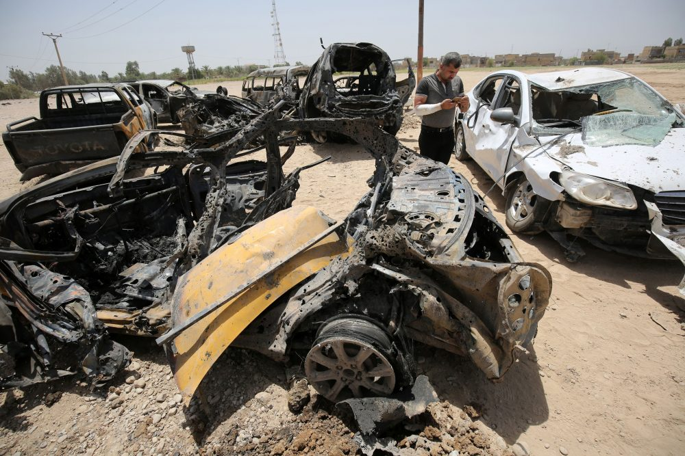 An Iraqi man stands next to damaged cars as he inspects the site of a suicide bomb attack, claimed by the Islamic State group, at a checkpoint leading to the Husseiniyah area, northeast of the capital Baghdad on July 13, 2016. (Ahmad Al-Rubaye/AFP/Getty Images)